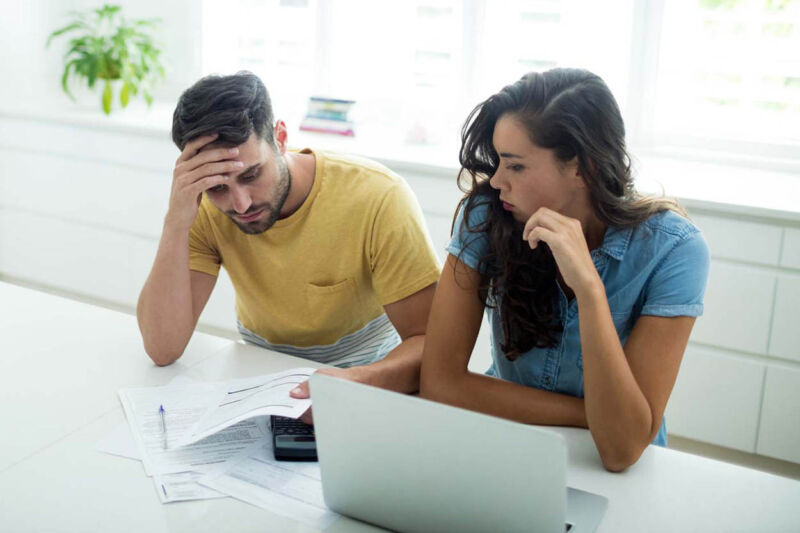 Worried couple calculating their invoices