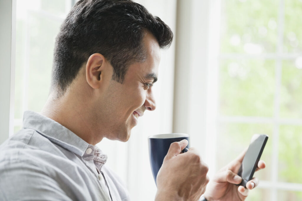 Man using smart phone while drinking coffee